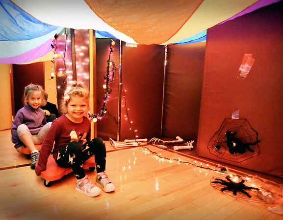 """BRYAN EATON/Staff Photo. Corryn DeMann, left, and Landry Desch, both 5, pull themselves along in scooters past bones and large spiders in a """"haunted house"""" made of mats and a parachute. The kindergartners were doing Halloween-themed physical activities like jumping under a giant spider web and tossing rings over withches hats."""