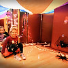 "BRYAN EATON/Staff Photo. Corryn DeMann, left, and Landry Desch, both 5, pull themselves along in scooters past bones and large spiders in a ""haunted house"" made of mats and a parachute. The kindergartners were doing Halloween-themed physical activities like jumping under a giant spider web and tossing rings over withches hats."