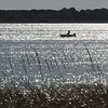 BRYAN EATON/Staff Photo. A silhouetted fisherman floats with the tide down the Merrimack River off Plum Island Point on Tuesday afternoon. Many boats upriver are off their moorings and the larger boats have started to be taken out to dry dock.
