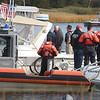 BRYAN EATON/Staff Photo. The U.S. Coast Guard, Newburyport Fire Department and harbormast responded to a man whose boat got away from him at Cashman Park and floated upriver with him clinging onto the side. They brought the craft to the docks at the North End Boat Club, seen here. He was uninjured in the mishap.