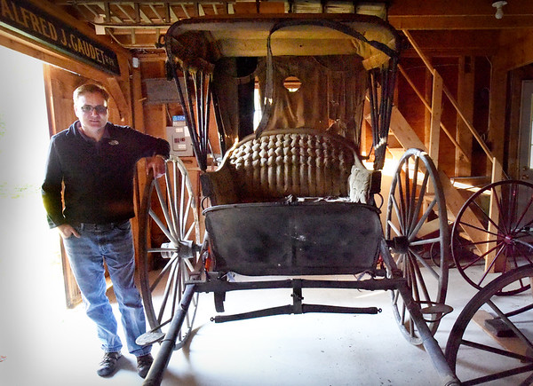 BRYAN EATON/Staff Photo. Jon Camp of the Bartlett Museum in Amesbury shows a carriage the organization has acquired from a farm in Maine. The carriage was built in Amesbury in 1855.