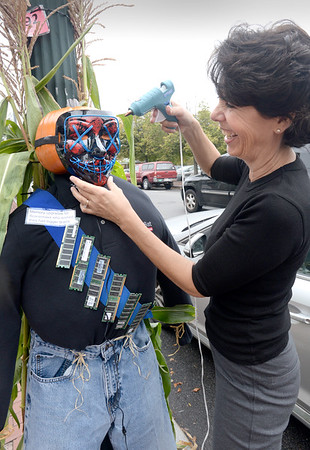 """BRYAN EATON/Staff Photo. Laura Soussan, co-owner of CommSat, an IT support company in downtown Amesbury, glues a mask that will light up onto a pumpkin head. Her scarecrow is an homage to the Wizard of Oz with a tag saying """"Memory upgrades for Scarecrows who wished they had bigger brains."""" usinesses, individuals and groups have been putting up the scarecrows in a contest sponsored by the Amesbury Chamber of Commerce and Industrial Foundation. People will cast their ballots starting Tuesday October 1 until October 15 with the winners being announced the next day for the different categories."""