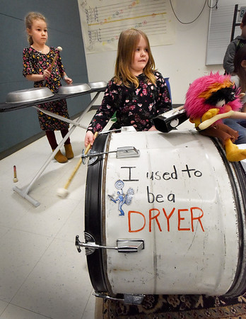 BRYAN EATON/Staff Photo. Second-graders Autumn Shamano, 7, left taps on old frying pans set up on an old ironing board as Lilliana Davis, 8, thumps a drum that used to be a dryer. Each grade is participating in the Junk2Funk but the fifth-graders will be getting special instruction and will be putting on a show at a later date.