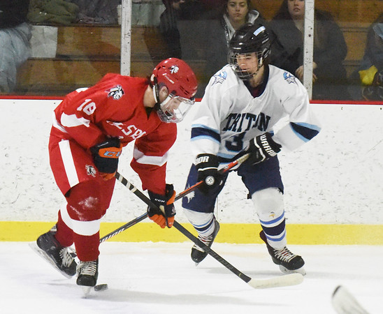 BRYAN EATON/Staff photo. Triton's Cam Murray tries to shoot the puck past Amesbury's Zach Begin, his skate stopping the shot.