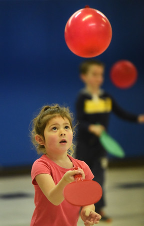 """BRYAN EATON/Staff Photo. Lilianna Sanfacon, 5, uses a ping pong paddle to strike a balloon in Margaret Welch's physical education class at Amesbury Elementary School. Once a week the kindergartners do a """"striking"""" excercise which helps with their eye to hand coordination."""