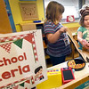 BRYAN EATON/Staff Photo. Allessandra Petiti, 5, right takes a pizza out of the oven as Peyton Bryant, 5, prepares the to-go box at the Preschool Pizzeria in Julie Deschene's class at Salisbury Elementary School. The pizza shop was one of the learning centers in the classroom where the youngsters learn role playing, Allessandra as the chef and Peyton as the hostess.
