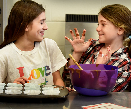 BRYAN EATON/Staff Photo. AnnaMae McKanas, 9, right, threatens to put chocolate cupcake batter on Riley Anne Tarney's, 11, face which she got on her fingers while mixing it up. The two were at the Boys and Girls Club in Salisbury during Cupcake Madness on Friday afternoon. After the cookies were baked, the youngsters decorated them for the counselors to judge for most creative.