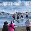 BRYAN EATON/Staff photo. Dozens of hearty souls jumped into the Atlantic Ocean at Salisbury Beach as others were content to watch. Following tradition they heading into the  frigid water after running in the Hangover Classic 5K and !0K races on New Year's Day.