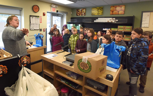 BRYAN EATON/Staff Photo. AmeriCorps VISTA member Melanie Bouchard gives Amesbury Elementary School student council members a tour of Our Neighbors Table. The students are holding a food drive for the agency and wanted to have a first hand look at the operation.