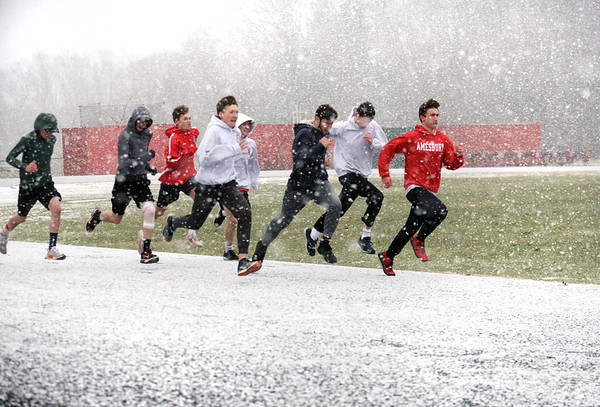 BRYAN EATON/Staff Photo. A snow squall blew through Amesbury just before 4:00p.m. on Wednesday afternoon, with the sun appearing 15 minutes later. That didn't stop the Amesbury High indoor track team, who went out to practice, from running some laps around the track.