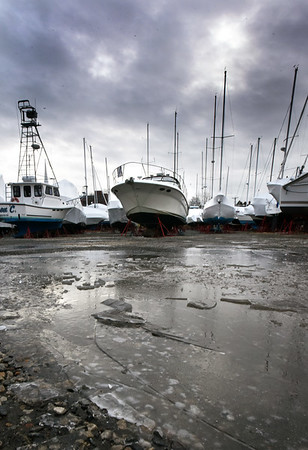 BRYAN EATON/Staff Photo. The sun tries to break through some clouds over the masts of boats in storage at the Windward Yacht Yard in Newburyport in a wintry scene on Monday afternoon. It won't be so wintry this weekend as the high temperature is forecast to be 57 degrees though with rain.
