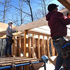 BRYAN EATON/Staff Photo. Cody Littlefield, left, Aristotle Campbell lift a joist atop the first floor of one of the homes.