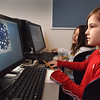 BRYAN EATON/Staff Photo. Pam Jamison's art class moved from the art room to the computer lab creating snowflakes on the computer with images of objects of nature in the makeup of the flake. The Make-a-Flake program uses visual thinking and strategy to make the design of the snowflakes shown by Ruby Wallace, 9, back, and Chloe Smith, 8.