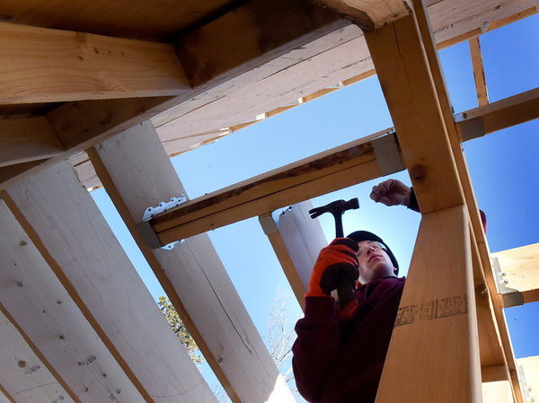 BRYAN EATON/Staff Photo. Aristotle Campbell hammers hangers which help support the joists.