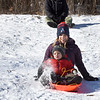 BRYAN EATON/Staff Photo. Jackson Thomen-Brown, 2, kicks up some snow as he sleds with his parents Renee and Zach on Monday. The Salisbury family was at March's Hill in Newburyport making the best of the weekend's snowstorm.
