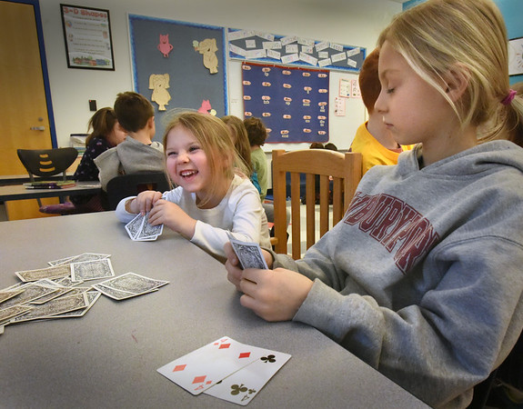 BRYAN EATON/Staff Photo. Everly Adams, 5, left, reacts as Layla LeClair, 8, calls for a card she has in a game of Fish in Linda Gershuny's kindergarten class at the Bresnahan School in Newburyport. The kindergartners watched a Boosterthon video on honesty and they paired with their third grade reading buddies in Laurie Barrows' class to encourage them to be honest, the game of cards as an example.