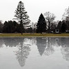 BRYAN EATON/Staff photo. Trees are reflected in the melted ice on the Frog Pond in Newbury's Upper Green, not good for ice skaters. It's not likely to freeze for awhile as the only daytime high above freezing this week is on the Thursday with rain and tempeatures in the low 50's forecast for Saturday.
