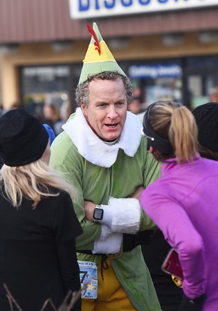 BRYAN EATON/Staff photo. Chris Donovan of Amesbury, dressed as Elf, chats with fellow runners at the Hangover Classic Roadrace at Salisbury Beach on New Year's Day. He said he was running with the hat on and planned to jump in the ocean at the end of the 5K race while looking for candy canes along the route he quipped.