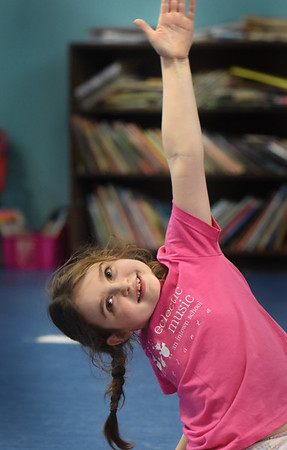 BRYAN EATON/Staff Photo. Eleanor Remignanti, 7, warms up in yoga class at Newbury Elementary School, one of the offerings of the school's afterschool program Explorations. The six week course, which meets on Mondays, is led by Elissa Shoreman of Buddhaful Souls Yoga Studios in Rowley.