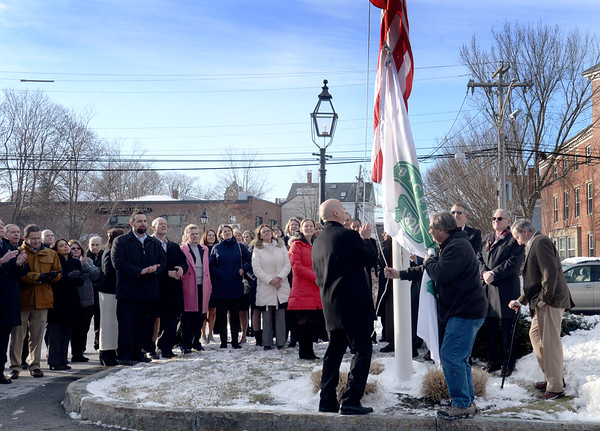 BRYAN EATON/Staff Photo. Institution for Savings President and CEO Michael J. Jones, center, hoist the 200th anniversary flag outside the Newburyport bank on Tuesday afternoon.