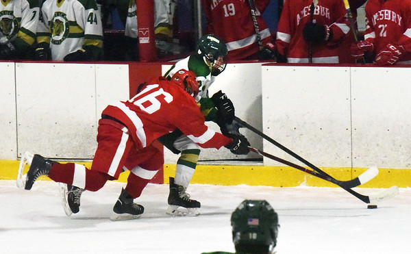 BRYAN EATON/Staff photo. Amesbury's # 16 tries to wrest control of the puck from Jack Stewart.