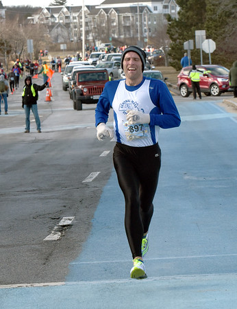BRYAN EATON/Staff photo. Nate Jenkins of North Andover is the winner in the 5K race in the Hangover Classis at Salisbury Beach.
