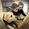"BRYAN EATON/Staff Photo. Nico Azul, center, and Emma Smith, both 8, read ""The Magic Hat"" to Tracker, also 8, at the Pine Grove School in Rowley. The yellow lab is the pet of assistant Principal Nicole LaPerriere who brings Tracker to the school three days a week and greets students as they come into school. The certified therapy dog gets read to by students in a nonjudgemental environment which allows students to enjoy reading, build confidence as they can read at their own pace."