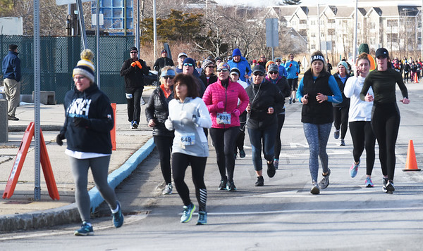 BRYAN EATON/Staff photo. Runners make the turn onto Cable Avenue in the Hangover Classis at Salisbury Beach.