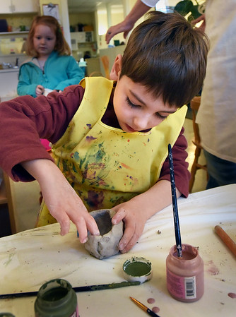 BRYAN EATON/Staff Photo. Nolan Salsky, 5, turns a piece of clay around using his fingers to move to clay outward as he makes a pinch pot at the Newburyport Montessori School. Local artist and potter Ann Healy was on hand to teach youngsters about the history and uses of pottery. After the works are completed, Lloyd Hamovit at 2 Rivers Ceramic Studio in Newbury will fire the pots for free.