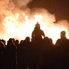 BRYAN EATON/Staff photo. One youngster gets a good view of the bonfire sitting on the shoulders of their parent as snow started to fall.
