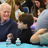 BRYAN EATON/Staff Photo. Eamon McDonnell of Ipswich chats with his grandsons Roland Byrne, 10, and Aidan, 13, of West Newbury at the Immaculate Conception School's VIP Luncheon, part of Catholic Schools Week.