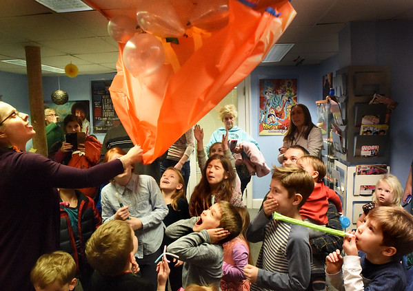 """BRYAN EATON/Staff Photo. Youngsters react as Amesbury Public Library Children's Librarian Clare Dombrowski releases balloons after counting down at their """"Noon Year's Eve Party."""" Children had snacks and did crafts and Tuesday at noon counted down for the balloon release complete with blowers and a bubble machine making for a festive occaision twelve hours before actual New Year."""