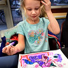 BRYAN EATON/Staff Photo. Greta Jones, 7, of Newburyport checks out the progress of the very colorful unicorn she's creating in the Children's Room at the Newburyport Public Library. She was at Cookies and Coloring with her sister, Lucy, 7, and grandmother Laura Peterson of Newburyport.