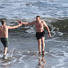 BRYAN EATON/Staff photo. Mark Zytkovicz of Andover gets a high five from a fellow bather as he exits the Atlantic Ocean at Salisbury Beach. He was the first one in the frigid water after running in the Hangover Classic 5K and !0K races on New Year's Day.