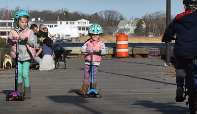 BRYAN EATON/Staff photo. Scores of people were out this weekend at the beaches, railtrails and here on the boardwalk in Newburyport's waterfront where sisters Wren Wentworth, 5, left, Alice, 2, of Newburyport moved along on there scooters. Though it was windy, Saturday hit 67 degrees with 70 on Sunday as the wind died down in the afternoon.