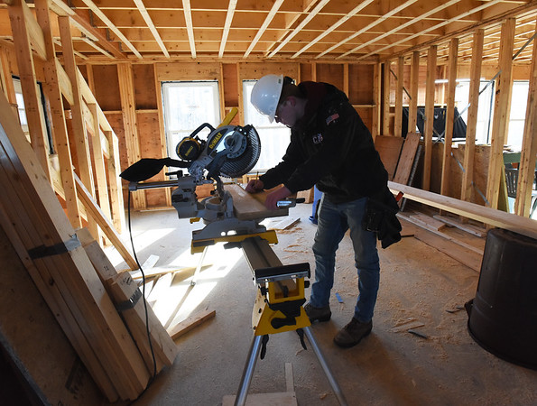 BRYAN EATON/Staff Photo. Ethan Burridge uses a chopsaw to cut blocks to be used between joists.
