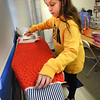 BRYAN EATON/Staff Photo. Sadie Crowell, 12, irons out a piece of fabric that she's making a pillow with at the sewing class at the Boys and Girls Club in Salisbury. Elizabeth Lascelles, vice president of design at Bennett and Co. in Newburyport is helping instructor Judy Gaffney on occasion.