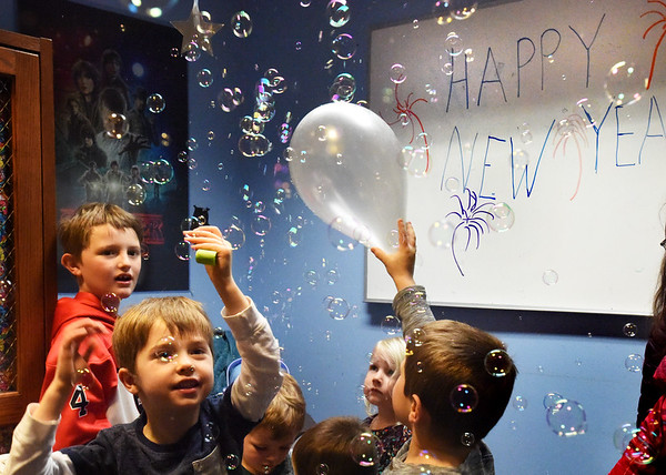 BRYAN EATON/Staff Photo. Youngsters try to pop the bubbles in the air at the Noon Year's Eve Party.