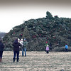 BRYAN EATON/Staff photo. People check out the huge pile of Christmas trees to be burned at the Old Newbury Bonfire in one of Tendercrop Farm's fields. The annual event benefits Newbury Volunteer Fire Department Protection #2.