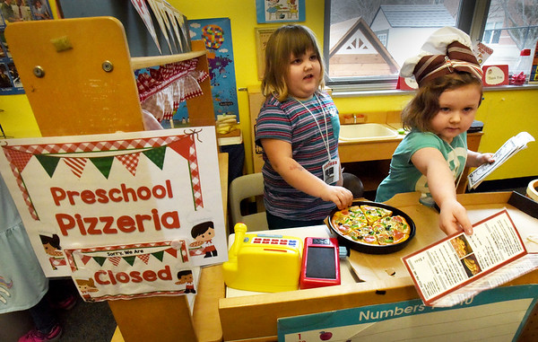 """BRYAN EATON/Staff Photo. Allessandra Petiti, 5, hands out a take-out menu to a """"customer"""" as Peyton Bryant, 5, slides a pizza into a to-go box at the Preschool Pizzeria in Julie Deschene's class at Salisbury Elementary School. The pizza shop was one of the learning centers in the classroom where the youngsters learn role playing, Allessandra as the chef and Peyton as the hostess."""
