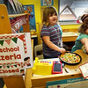 "BRYAN EATON/Staff Photo. Allessandra Petiti, 5, hands out a take-out menu to a ""customer"" as Peyton Bryant, 5, slides a pizza into a to-go box at the Preschool Pizzeria in Julie Deschene's class at Salisbury Elementary School. The pizza shop was one of the learning centers in the classroom where the youngsters learn role playing, Allessandra as the chef and Peyton as the hostess."