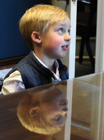 BRYAN EATON/Staff Photo. Oliver Egmont, 4, recollects his third recollection for Amesbury Mayor Kassandra Gove.