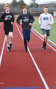 BRYAN EATON/Staff Photo. Triton track star Graham Stedfast, center, has set new school records in the mile for both indoor and outdoor track and is starting to look like a possible all-time great for the Triton distance program.