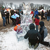 BRYAN EATON/Staff photo. People mill around an ice scupture in the shape of flames while eating and drinking items from vendors at the Old Newbury Bonfire on Saturday. Hayrides were available along with tours of the Spencer-Peirce-Little Farm before the lighting of the Christmas trees.