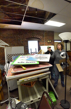 BRYAN EATON/Staff Photo. Amesbury Community Theater stage manager Susan Balaam, left, and owner Michelle Spadafora, among the damaged items from a water leak in the ceiling above.