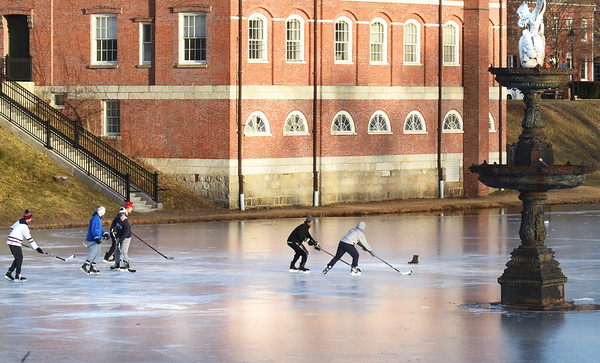 BRYAN EATON/Staff Photo. Late afternoon sun reflects on Newburyport Superior Court late Thursday afternoon onto skaters passing around a hockey puck past the water fountain in the Frog Pond at the Bartlet Mall in Newburyport. There's open water in the northeast section of the pond which could expand as temperatures touching the 60's is forecast tomorrow with rain possible on Sunday.
