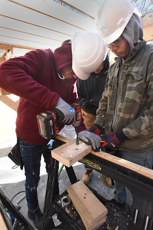 BRYAN EATON/Staff Photo.  Jyrell Ruiz and Tyler Wetherbee drill holes in blocks for lag screws to the frame for temporary support.