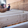 BRYAN EATON/Staff Photo. Jacob Goodhue nails joists into the anchor joist.