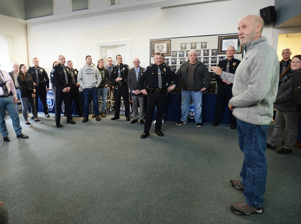 BRYAN EATON/Staff Photo. Former Amesbury police chief Mark Gagnon was one of several people lauding retiring Amesbury Police Sgt. Rick Poulin, center, who is retiring.