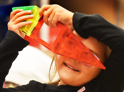 BRYAN EATON/Staff Photo. Kindergartners in LInda Gershuny's class at the Bresnahan School in Newburyport grabbed items from different boxes to become creative and explorative in some STEM-themed time. Gia Campbell, 6, took some plastic colored tiles that click together to make different shapes and created the shape of an ice cream cone, then noticed she could see the world in a different light looking through a red tile.